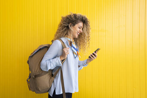 Smiling young woman with backpack in front of yellow background looking at cell phone - DAMF00162