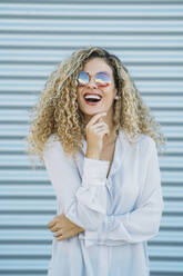 Portrait of laughing young woman with sunglasses - DAMF00165