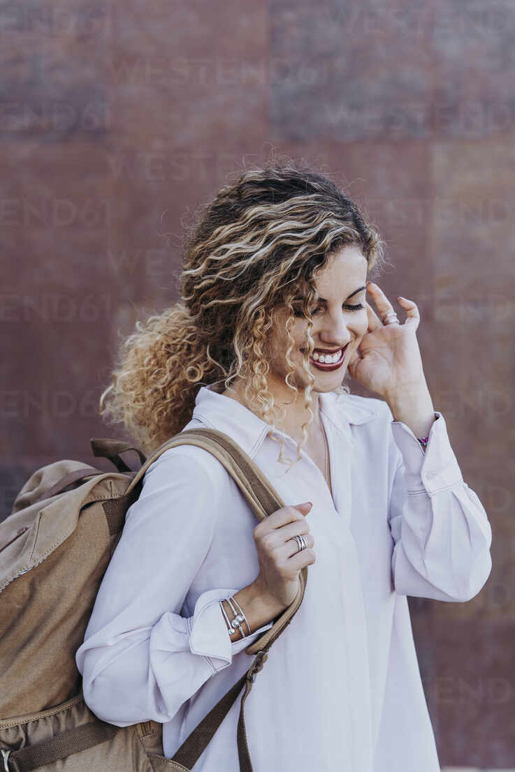 Portrait of happy young woman with backpack - DAMF00171 - David Agüero Muñoz/Westend61
