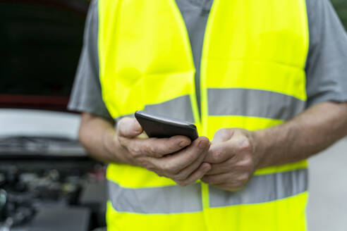 Close up of a senior man standing at his broken car wearing a safety vest and using his smartphone - AFVF04054