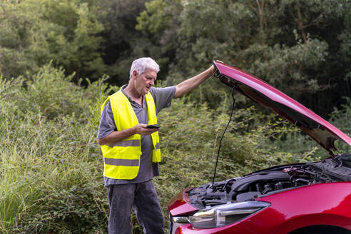 Senior man standing at his broken car wearing a safety vest and using his smartphone - AFVF04057