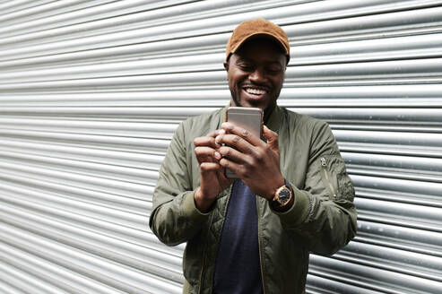 Portrait of laughing man taking selfie with smartphone - IGGF01369