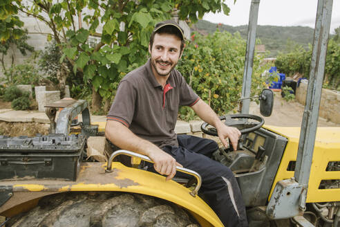 Portrait of a smiling farm tractor driver in a vineyard - AHSF00918