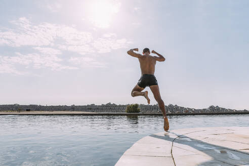 Young man jumping into water from a pier - MOSF00048