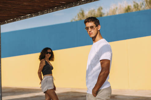 Cool young couple wearing sunglasses standing outdoors in summer - MOSF00066