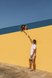 Young man reaching out for woman behind a yellow wall - MOSF00069