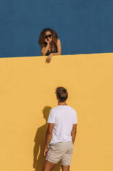 Young man looking at woman behind a yellow wall - MOSF00072