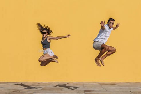 Young couple jumping in front of a yellow wall - MOSF00075