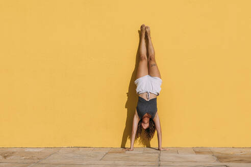 Young woman doing a handstand in front of a yellow wall - MOSF00078