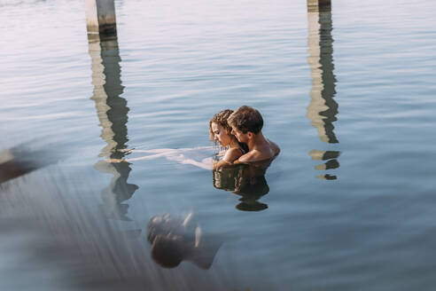 Affectionate young couple bathing in the sea - MOSF00087