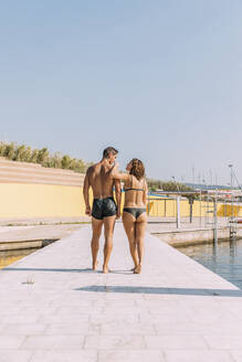 Young couple walking on a pier at the sea - MOSF00090