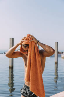 Young mna drying his hair with a towel at the sea - MOSF00093