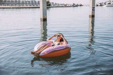 Young woman bathing in the sea on inflatable float in donut shape - MOSF00099