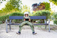 Boy wearing a space suit and sitting on a bench, using tablet - CJMF00123
