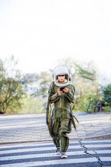 Boy wearing a space suit, crossing road and using smartphone - CJMF00129