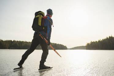 Man ice-skating on frozen lake - JOHF03022