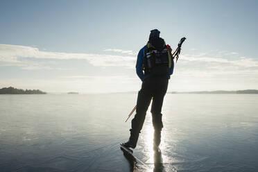 Man ice-skating on frozen lake - JOHF03025