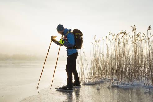 Man ice-skating on frozen lake - JOHF03031