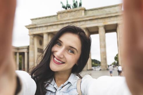 Selfie of happy young woman at Brandenburg Gate, Berlin, Germany - WPEF02039