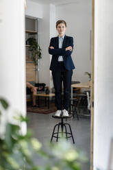 Portrait of a confident businesswoman standing on a stool - KNSF06736