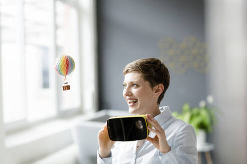Smiling woman with VR glasses and small hot-air balloon in office - KNSF06745