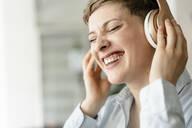 Portrait of happy businesswoman listening to music with headphones - KNSF06748