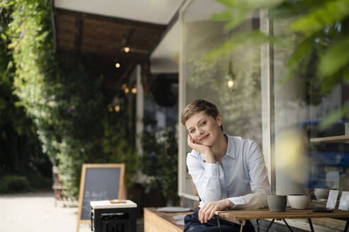 Portrait of smiling businesswoman at a cafe - KNSF06760
