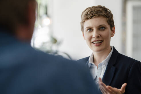 Portrait of businesswoman talking to a colleague - KNSF06766