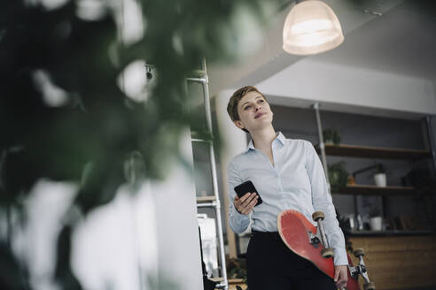 Businesswoman with cell phone and skateboard in a cafe - KNSF06778