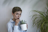 Portrait of businesswoman drinking from potted plant - KNSF06784