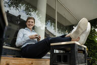 Portrait of a happy businesswoman relaxing at a cafe - KNSF06790