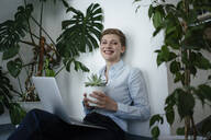 Portrait of a businesswoman with laptop sitting on the floor surrounded by plants - KNSF06796