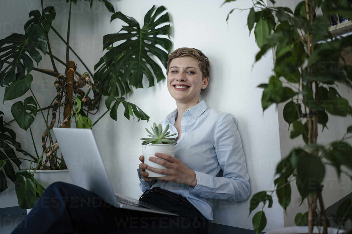 Portrait of a businesswoman with laptop sitting on the floor surrounded by plants - KNSF06796 - Kniel Synnatzschke/Westend61