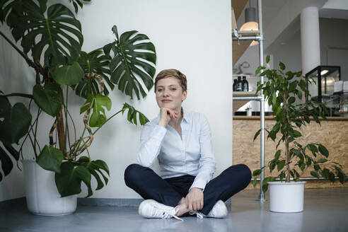 Portrait of a businesswoman sitting on the floor surrounded by plants - KNSF06799