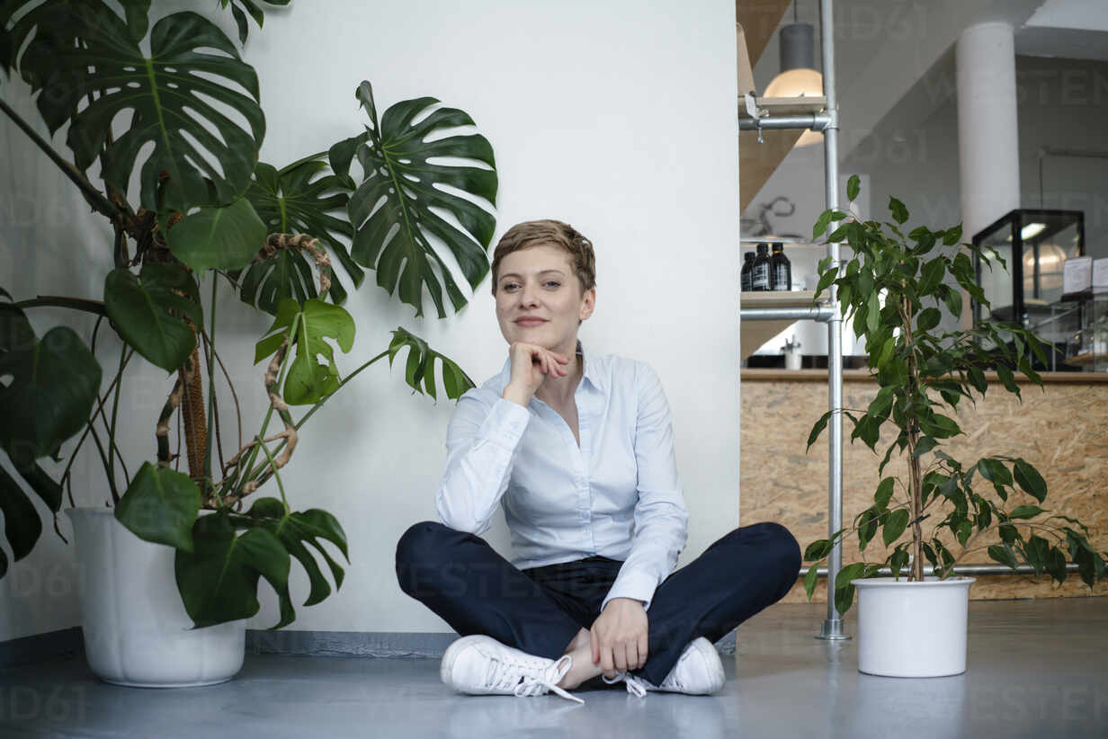 Portrait of a businesswoman sitting on the floor surrounded by plants - KNSF06799 - Kniel Synnatzschke/Westend61