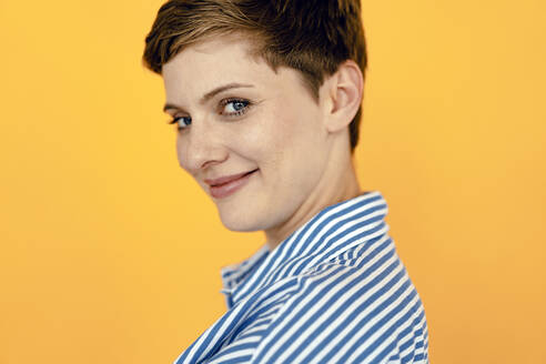 Portrait of smiling woman with orange background - KNSF06811