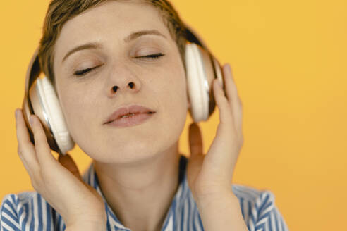 Portrait of woman listening to music with orange background - KNSF06814