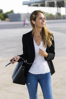 Smiling businesswoman with smartphone and earphones outdoors - GIOF07182