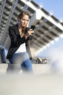 Businesswoman sitting on a wall with smartphone and earphones - GIOF07188