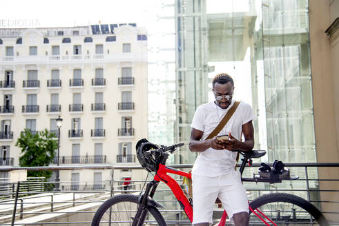 Young man at his bike using his smartphone - CJMF00136