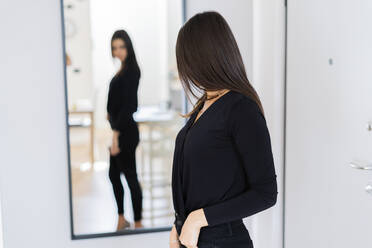 Young woman watching herself in mirror - GIOF07223