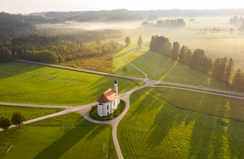 Germany, Bavaria, Dietramszell, Aerial view of countryside fields and Church of Saint Leonhard at foggy dawn - LHF00724