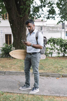 Casual businessman with skateboard using smartphone in the city - ALBF01153