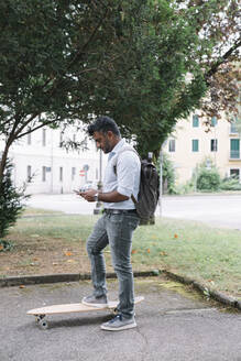 Casual businessman with skateboard using smartphone in the city - ALBF01156