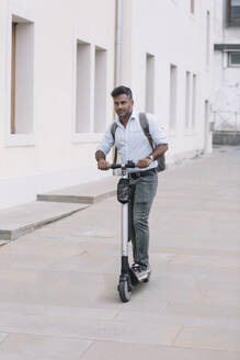 Casual businessman riding e-scooter in the city - ALBF01159