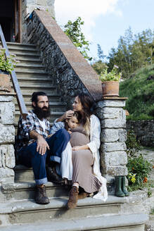 Family relaxing on stoop of a rustic house - SODF00101