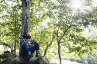 Man with beard relaxing at tree trunk in the forest - SODF00104
