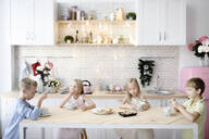 Four children eating cookies at kitchen table - EYAF00571