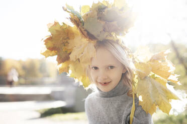 Portrait of smiling little girl with autumn wreath on her head - EYAF00591