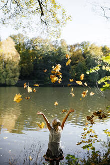 Back view of little girl standing at riverside throwing autumn leaves in the air - EYAF00597